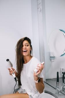 Junge schöne frau im badezimmer, die einen haartrockner und eine kleine flasche hält, nahe ansicht