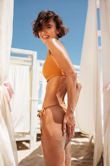 Junge schöne frau im beige bikini, der am strand steht und sich sonnt. porträt des lächelnden mädchens, das hände auf ihrem gesäß hält und glücklich schaut