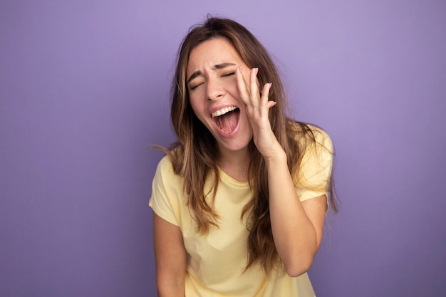Junge schöne frau im beigen t-shirt aufgeregt und glücklich mit der hand in der nähe des mundes schreien