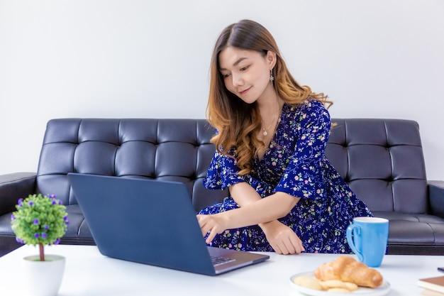 Junge schöne frau im blauen kleid, das an ihrem computer in ihrem hauptwohnzimmer arbeitet