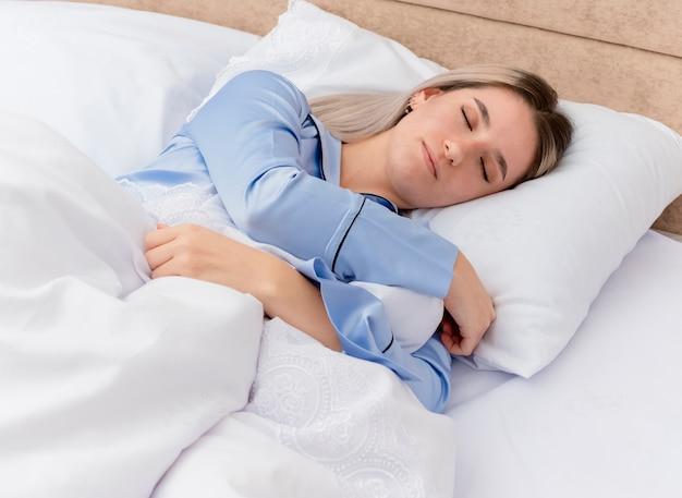 Junge schöne frau im blauen pyjama, der auf bett liegt, das auf weichen kissen ruht, die friedlich zu hause im schlafzimmerinnenraum auf hellem hintergrund schlafen