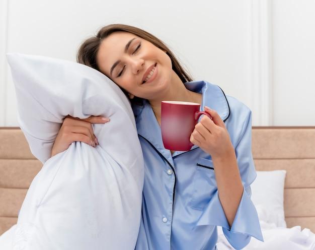 Junge schöne frau im blauen pyjama, der auf bett mit kissen und tasse kaffee sitzt, die positive emotionen mit geschlossenen augen im schlafzimmerinnenraum auf hellem hintergrund fühlen