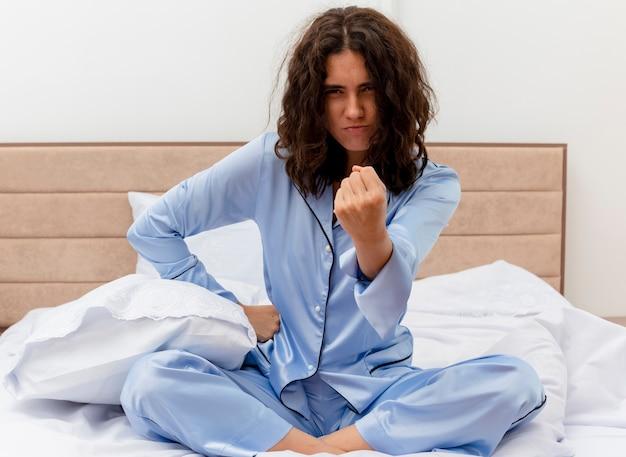 Junge schöne frau im blauen pyjama, der auf bett sitzt, das faust mit wütendem gesicht im schlafzimmerinnenraum auf hellem hintergrund zeigt