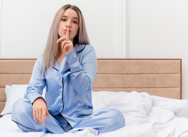 Junge schöne frau im blauen pyjama, der auf bett sitzt, das stille geste mit finger auf lippen im schlafzimmerinnenraum auf hellem hintergrund macht