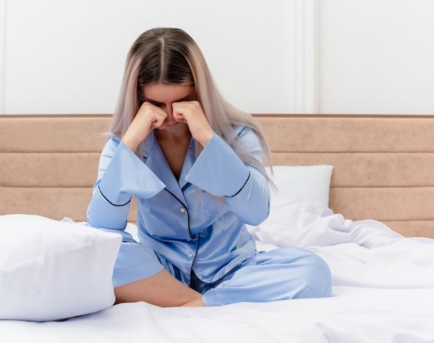 Junge schöne frau im blauen pyjama, der auf bett sitzt, reibt ihre augen, die im schlafzimmerinnenraum auf hellem hintergrund aufwachen