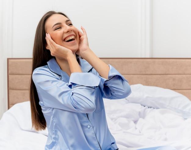 Junge schöne frau im blauen pyjama, der auf bett sitzt und beiseite schaut, im schlafzimmerinnenraum auf hellem hintergrund lachend