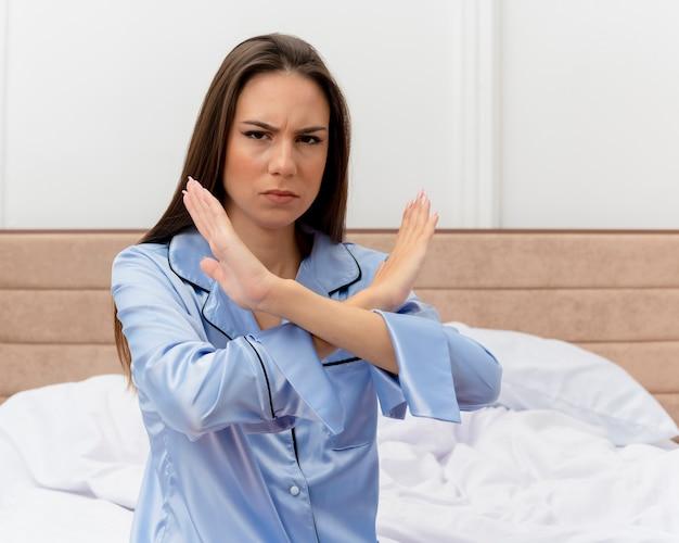 Junge schöne frau im blauen pyjama, der auf bett sitzt und kamera mit ernsthaften gesichtkreuzungshänden betrachtet, die stoppgeste im schlafzimmerinnenraum auf hellem hintergrund machen