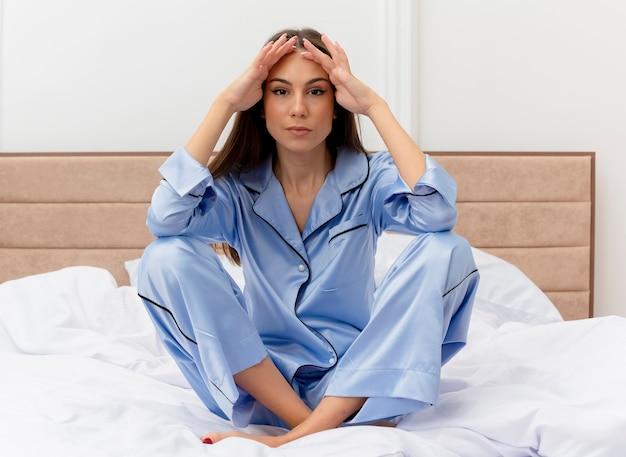 Junge schöne frau im blauen pyjama, der auf bett sitzt und kamera müde und gelangweilt im schlafzimmerinnenraum auf hellem hintergrund betrachtet