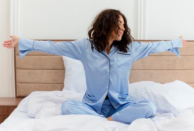 Junge schöne frau im blauen schlafanzug, der auf bett liegt