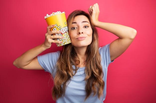 Junge schöne frau im blauen t-shirt, die eimer mit popcorn hält und die kamera glücklich und fröhlich lächelt, die über rosafarbenem hintergrund steht