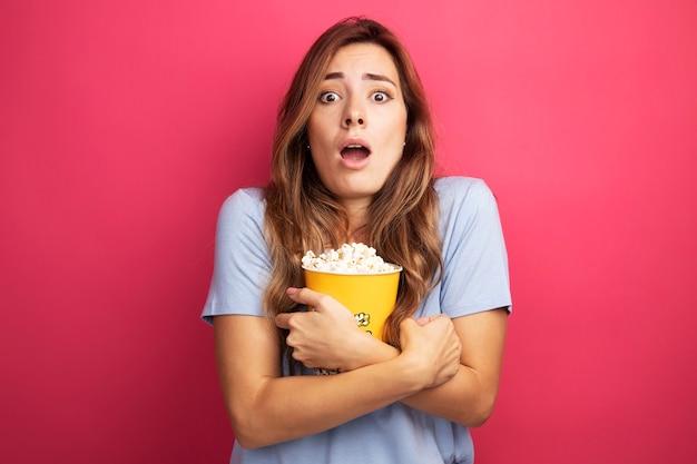 Junge schöne frau im blauen t-shirt, die eimer mit popcorn hält und in die kamera schaut, überrascht stehend über rosa hintergrund