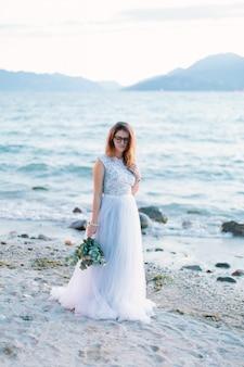 Junge schöne frau im eleganten blauen kleid, das den blumenstrauß hält und nahe dem gardasee, sirmione geht. lago di garda, italien
