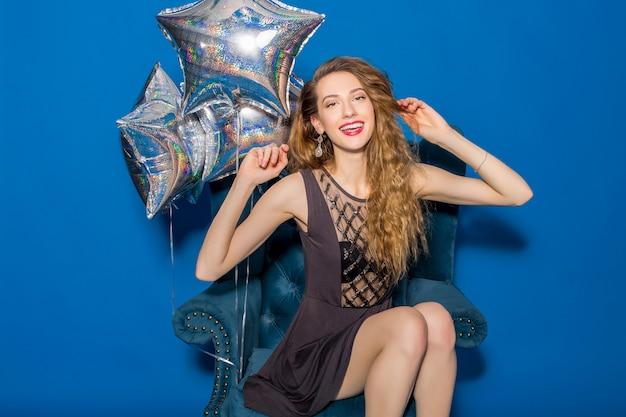 Junge schöne frau im grauen kleid, das auf einem blauen sessel mit silbernen luftballons sitzt