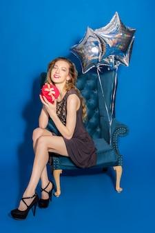 Junge schöne frau im grauen kleid sitzt auf einem blauen sessel, der geschenkbox hält