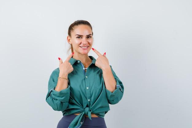 Junge schöne frau im grünen hemd, das auf ihre zähne zeigt und fröhlich schaut, vorderansicht.