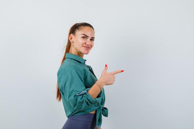 Junge schöne frau im grünen hemd, die nach rechts zeigt, während sie posiert und fröhlich aussieht, vorderansicht.