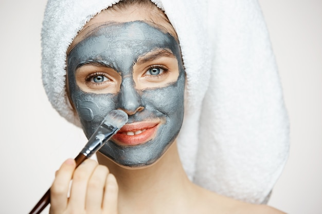 Junge schöne frau im handtuch auf kopfbedeckungsgesicht mit lächelnder maske. schönheitskosmetik und spa.