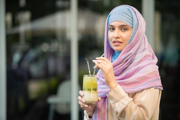 Junge schöne frau im hijab, der kühlenden cocktail vom glas trinkt, während im freien ruhen