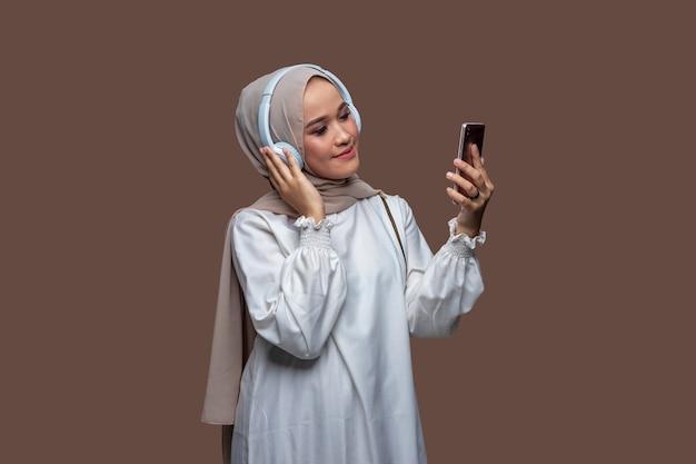 Junge schöne frau im hijab, die musik vom handy mit drahtlosen kopfhörern hört