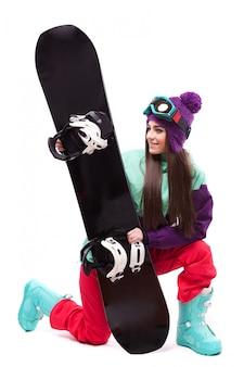 Junge schöne frau im lila skimantel stehen auf knie und halten snowboard