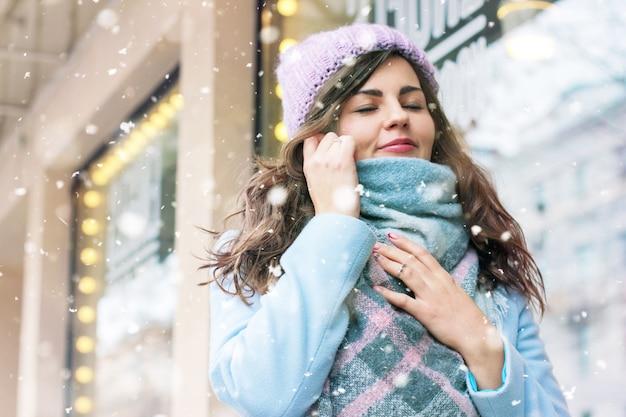 Junge schöne frau im mantel und im hut, die den ersten schnee enjoing sind
