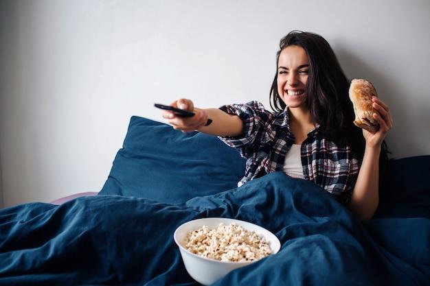 Junge schöne frau im morgenbett zu hause. fröhliche glückliche frau, die fernsieht. halten sie die fernbedienung in der hand und benutzen sie sie. frühstück mit popcorn und sandwich.