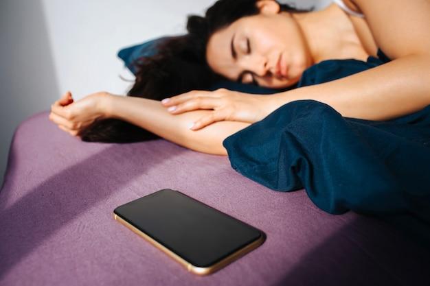 Junge schöne frau im morgenbett zu hause. schlafen und ausruhen. die sonne scheint nach innen. smartphone liegt neben frau auf ned.