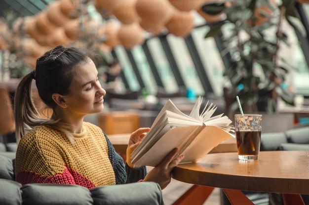 Junge schöne frau im orangefarbenen pullover, der interessantes buch im café liest
