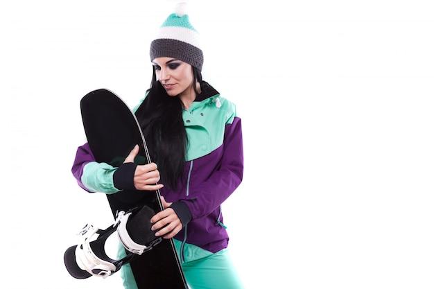 Junge schöne frau im purpurroten skianzuggriff snowboard
