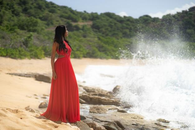 Junge schöne frau im roten kleid, das zum gebirgsmeer schaut. mädchen auf der natur auf blauem himmel. modefoto