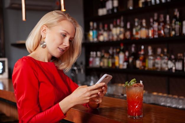 Junge schöne frau im roten kleid mit ihrem smartphone an der bar. frau, die nachricht auf ihrem telefon beim cocktail eintippt