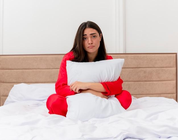 Junge schöne frau im roten pyjama, die im bett sitzt und kissen umarmt, unglücklich mit traurigem ausdruck im schlafzimmerinnenraum