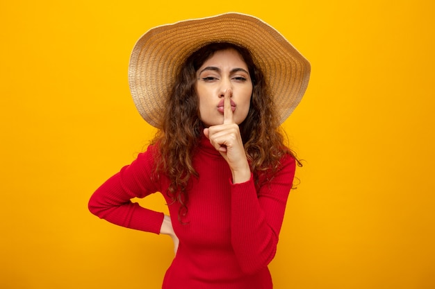Junge schöne frau im roten rollkragenpullover im sommerhut, die mit dem finger auf den lippen, die auf orange stehen, eine stillegeste macht