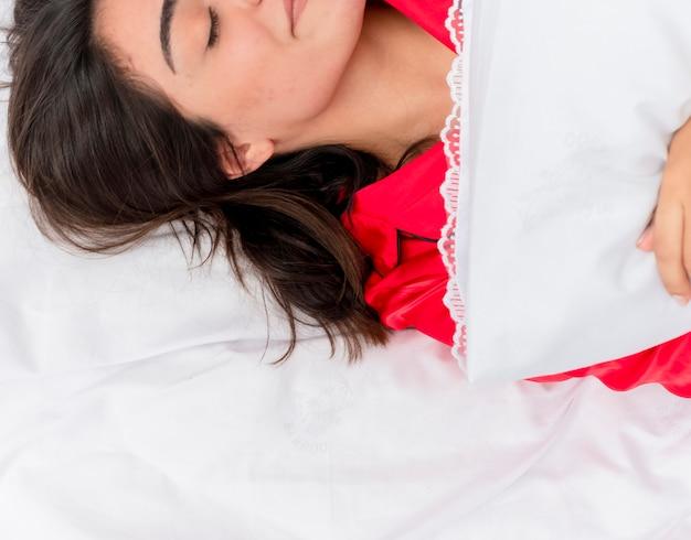 Junge schöne frau im roten schlafanzug, der auf bett liegt, das auf weichen kissen ruht, die friedlich im bett zu hause im schlafzimmerinnenraum auf hellem hintergrund schlafen