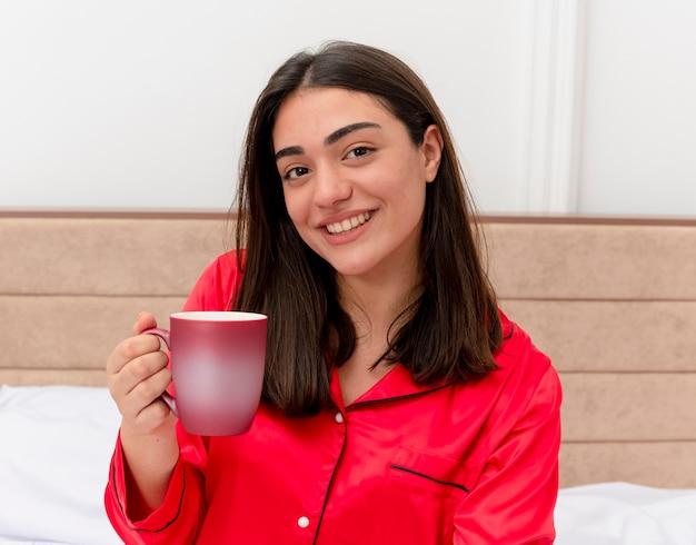 Junge schöne frau im roten schlafanzug, der auf bett mit tasse kaffee sitzt und kamera betrachtet, die fröhlich im schlafzimmerinnenraum auf hellem hintergrund lächelt