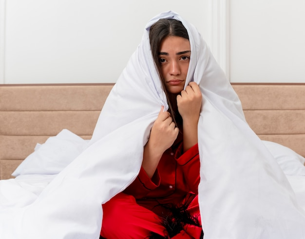 Junge schöne frau im roten schlafanzug, der auf bett sitzt, das in decke wickelt, die kamera mit traurigem ausdruck im schlafzimmerinnenraum auf hellem hintergrund betrachtet