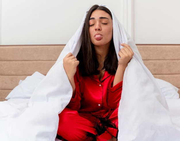 Junge schöne frau im roten schlafanzug, der auf bett sitzt, das in der decke wickelt, die heraussteckt zunge im schlafzimmerinnenraum auf hellem hintergrund entspannt