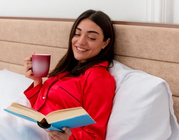 Junge schöne frau im roten schlafanzug, der im bett entspannt