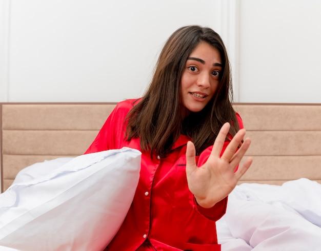 Junge schöne frau im roten schlafanzug, der im bett mit kissen sitzt, das stoppgeste mit hand macht, die im schlafzimmerinnenraum auf hellem hintergrund besorgt ist