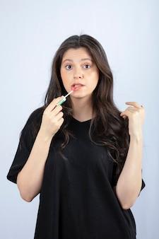 Junge schöne frau im schwarzen outfit, das lippenstift anwendet.
