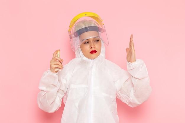 Junge schöne frau im speziellen weißen anzug, der spray auf rosa hält