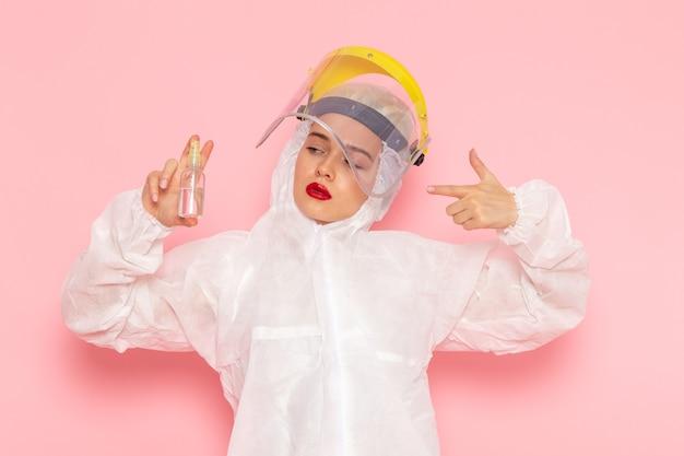 Junge schöne frau im speziellen weißen anzug, der sprühdose auf rosa hält