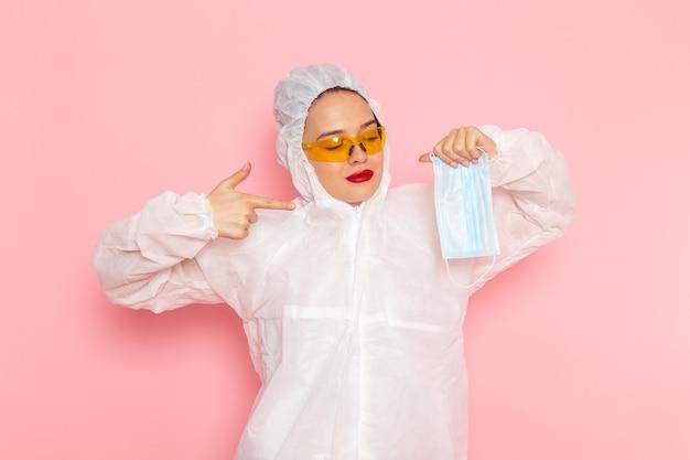 Junge schöne frau im speziellen weißen anzug, der sterile maske auf rosa hält