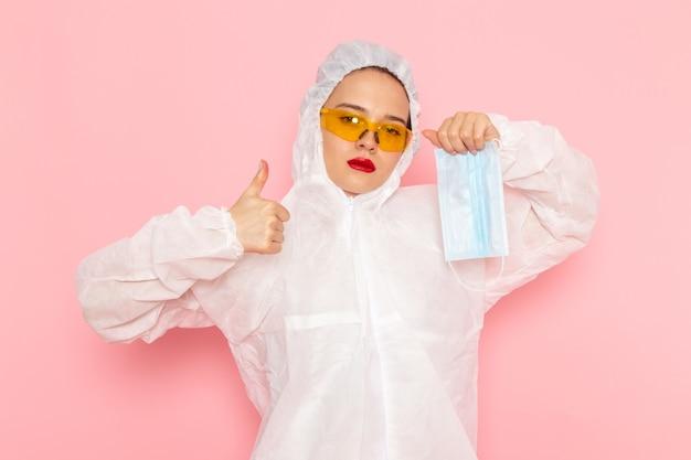 Junge schöne frau im speziellen weißen anzug, der sterile schutzmaske auf rosa hält