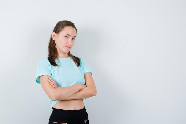 Junge schöne frau im t-shirt mit verschränkten armen und freudlosem blick, vorderansicht.