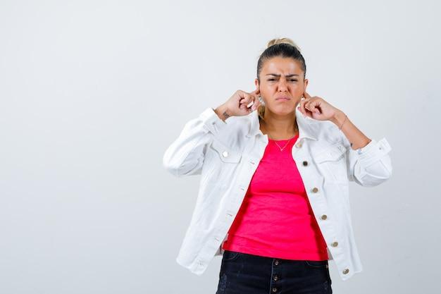 Junge schöne frau im t-shirt, weiße jacke, die ohren mit den fingern verstopft und genervt aussieht, vorderansicht.
