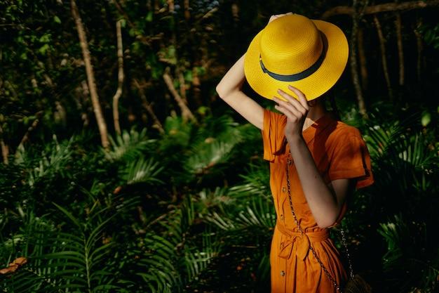 Junge schöne frau im tropendschungel mit hut geht in den park, naturforscher