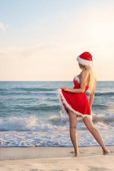 Junge schöne frau im weihnachtsmann-kostüm feiert weihnachten auf einer reise in warme länder am sandstrand des meeres