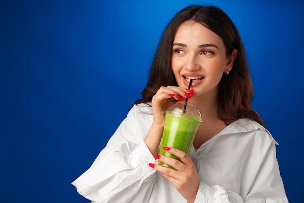 Junge schöne frau im weißen hemd trinkt grünen smoothie vor blauem hintergrund