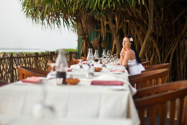 Junge schöne frau im weißen kleid am ufer des tropischen meeres in einem café. t